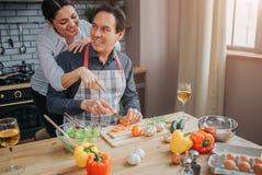 Support utile de femme derrière l'homme dans la cuisine Il s'asseyent à la table et la regardent Ils sourient entre eux Le type a photo libre de droits