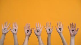 Support written palms on orange background, teamwork cooperation, activists