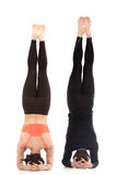 Supported headstand yoga asana in pair Stock Photos