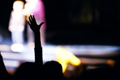 Supporter in the audience raising a hand. At a live performance silhouetted against the blurred outline of people on stage Royalty Free Stock Photography
