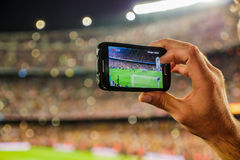Supporter football team recording goal with mobile phone camera. A supporter of F.C. Barcelona football team, recording a goal with his mobile phone camera at Royalty Free Stock Photography