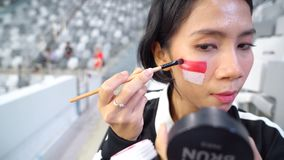 Supporter painting Indonesian flag on face. Female supporter painting Indonesian flag on her face during Asian Games 2018 competition in stadium. Shot in 4k stock footage