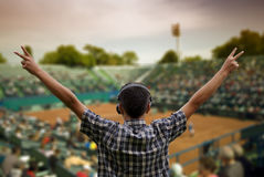 Supporter at tennis cup,clipping path. Supporter at tennis cup,hands raised with victory sign and headphones on his head,clipping path included Stock Photo