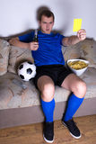 Supporter watching football on tv at home. With beer and chips and showing yellow card Stock Photography