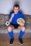Supporter watching football on tv at home and eating chips. Supporter in uniform watching football on tv at home and eating chips Stock Photography
