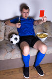 Supporter watching football on tv at home and showing red card. Supporter watching football on tv at home and showing penalty card Royalty Free Stock Photos