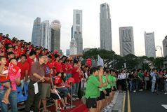 Supporters with city backdrop. Supporters during the Youth Olympic Games 2010 The Final Countdown Event in Singapore with the city as a backdrop stock photos