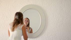 Supporti bianchi d'uso del vestito dalla giovane donna attraente davanti ad uno specchio stock footage