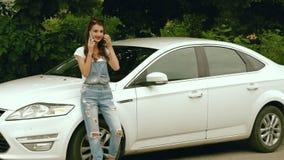 Supporti castana alla moda accanto alla sua automobile e parlare sul telefono archivi video