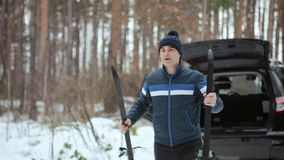 Supporti dell'uomo con gli sci vicino all'automobile nella foresta di inverno