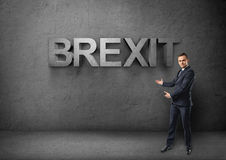Supporti dell'uomo d'affari che mostrano grandi 3d & x27; brexit& x27; parola da entrambe le mani su fondo concreto Fotografie Stock