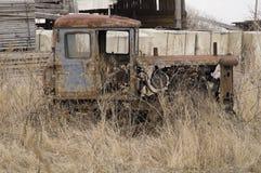 Supporti rari del coltivatore del trattore a cingoli abbandonati nell'erba Fotografia Stock
