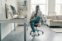 Supporting clients. Thoughtful young man in shirt and tie using smart phone while sitting in the office stock images