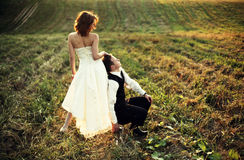 Supporting - groom rests on bride's legs somewhere on the field. A stock photography