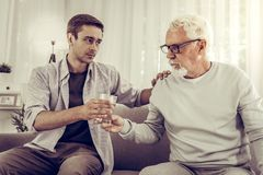 Supporting man handing the glass of water to elderly mister royalty free stock photo