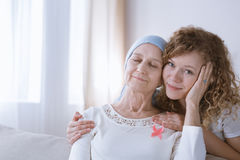 Supporting mother during cancer therapy. Young daughter supporting her sick mother during breast cancer therapy Royalty Free Stock Photography