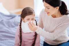 Supporting mother helping her child with a running nose Royalty Free Stock Images