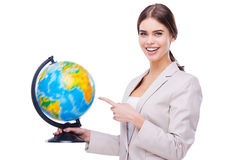 Supporting your business all around the world. Beautiful young woman holding globe and pointing on it while standing against white background royalty free stock image