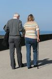 Supportive. Elderly man helping a middle aged female to walk with a walking stick, with a blue sky and the sea , out of focus, to the rear Royalty Free Stock Photo
