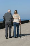 Supportive. Elderly man helping a middle aged female to walk with walking sticks, with a blue sky to the rear Stock Photos