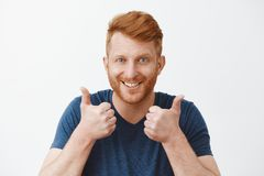 Supportive and attractive adult redhead male with bristle liking great plan raising hands, showing thumbs up, smiling. Joyfully, accepting nice idea or cheering stock photos