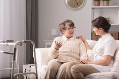 Supportive carer and patient. Supportive young carer sitting with older patient Royalty Free Stock Photography