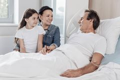 Supportive family visiting their husband and father in hospital. So happy to see you. Positive minded wife and daughter smiling while looking at their soulmate Stock Photos
