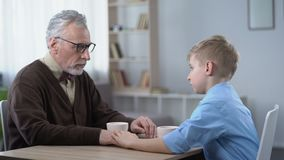 Supportive kid stroking grandpas hand, family going through hard times together. Stock footage stock footage