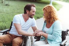 Supportive mature couple in wheelchairs chatting and smiling. Joyful conversation. Adorable mature couple sitting in wheelchairs and gossiping while spending stock photos