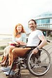 Supportive mature couple in wheelchairs smiling cheerfully. Enjoying our life. Positive minded husband and wife holding their hand together and smiling royalty free stock images