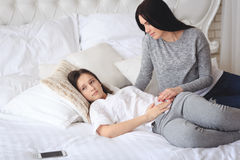 Supportive mother helping her worried teenage daughter. Lying on the bed Stock Photos