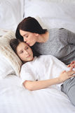 Supportive mother helping her worried teenage daughter. Lying on the bed Royalty Free Stock Photos