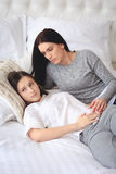 Supportive mother helping her worried teenage daughter. Lying on the bed Royalty Free Stock Photo