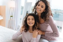 Supportive siblings posing for camera and smiling cheerfully. Harmonious family circle. Loving sisters spending their free time together at home and embracing Royalty Free Stock Photo