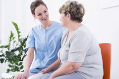 During the supportive talk. Young nurse and elder women sitting in clinic corridor and talking Royalty Free Stock Image