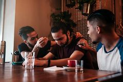 Supportive young men encourage their brokenhearted friend. Arabian guys cheer him up in restaurant. Friendship concept. Supportive young men encourage their Stock Image