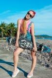 Supporto abbastanza sexy della giovane donna con il longboard davanti al mare e palme in tempo soleggiato Sport attivo facente fe Fotografia Stock Libera da Diritti