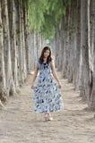 Supporto asiatico della ragazza sulla strada che hanno 2 pini laterali allineati Fotografie Stock Libere da Diritti
