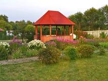 Supporto conico di legno in giardino floreale al tramonto Fotografie Stock