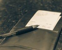 Supporto d'annata del cuoio di tono con il controllo e la penna della fattura del ristorante fotografie stock