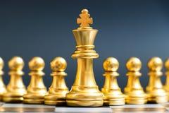 Supporto del pezzo degli scacchi di re dell'oro davanti al pegno su fondo nero immagini stock