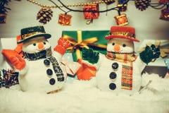 Supporto del pupazzo di neve fra il mucchio di neve alla notte silenziosa con una lampadina, un Buon Natale e la notte del nuovo  Fotografia Stock Libera da Diritti