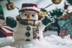 Supporto del pupazzo di neve fra il mucchio di neve alla notte silenziosa con una lampadina, un Buon Natale e la notte del nuovo  Immagini Stock