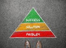 Supporto dell'uomo d'affari che affronta alla piramide di successo, della soluzione e di problema Fotografie Stock