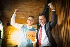 Supporto dell'uomo d'affari di due asiatici ed esaminare compressa, essi allegri e celebrati il suo riuscito nella missione immagine stock
