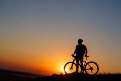Supporto dell'uomo della siluetta con il mountain bike sul prato Fotografia Stock Libera da Diritti