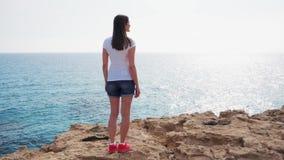 Supporto della donna al bordo della scogliera il giorno soleggiato al rallentatore Sguardo femminile spensierato alla vista del m stock footage