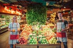 Supporto della donna e del giovane ai contenitori di frutta in drogheria Tengono l'agrume nelle mani e nel sorriso I lavoratori g immagini stock