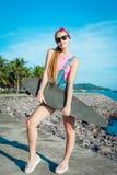 Supporto della giovane donna con il longboard davanti al mare e palme in tempo soleggiato Femmina sorridente di divertimento svag Fotografia Stock