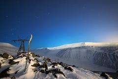 Supporto della linea ad alta tensione Un paesaggio della montagna di notte di inverno Fotografia Stock Libera da Diritti